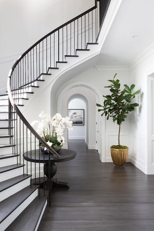 curved-staircase-wall-round-black-table-gold-planter-fiddle-leaf-fig